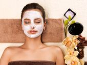 Portrait of beautiful young healthy woman with mask on her face relaxing in the spa salon. Beauty tr poster