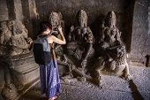 Girl Tourist Shooting A Photo On A Smartphone While Walking In A Temple Complex. Kailash Temple In E poster