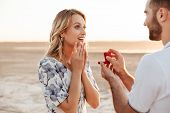 Photo of romantic man making proposal to his amazed woman with ring in gift box while walking on sun poster