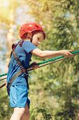 Boy Enjoying Activity In Climbing Adventure Park At Sunny Summer Day. Kid Climbing In Rope Playgroun poster