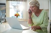 Senior woman talking on mobile phone while using laptop at home poster