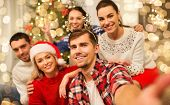 celebration and holidays concept - happy friends with glasses celebrating christmas at home party an poster