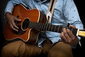 Male Guitar Musician Playing His Acoustic Guitar Isolated Black Background. poster