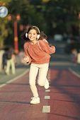 Giving All Her Best. Having Fun. Little Girl Running Outdoor. Little Girl Listen Music. Mp3 Player.  poster