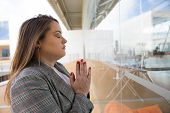 Focused Young Woman Praying With Closed Eyes. Side View Of Young Woman Praying In Office. Religious  poster
