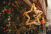 Christmas Street Decor. Stylish Christmas Golden Star Illumination And Fir Branches With Red And Gol poster