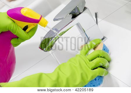 Cleaning - cleaning bathroom sink with spray detergent - housework, spring cleaning concept