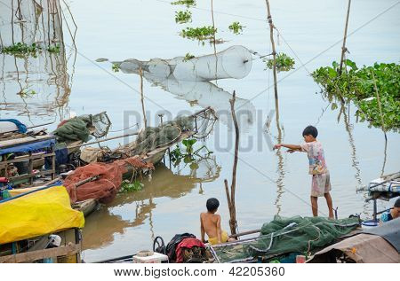 CHAU DOC, VIETNAM - JANUARY 2: Unidentified fisherman's children play on their boat waiting for the dinner on January 2, 2013, in Chau Doc, Vietnam. Fishing is an important source of incomein Vietnam.