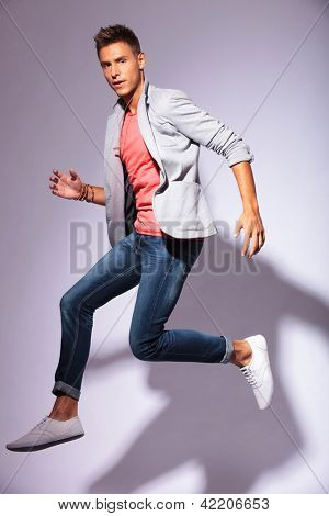 portrait of a jumping casual young man looking at the camera, over light background