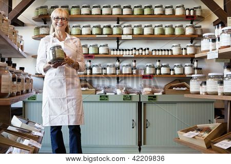 Portrait of a happy senior merchant standing with spice jar in store