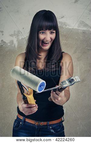 shoked girl holding tools over grunge background
