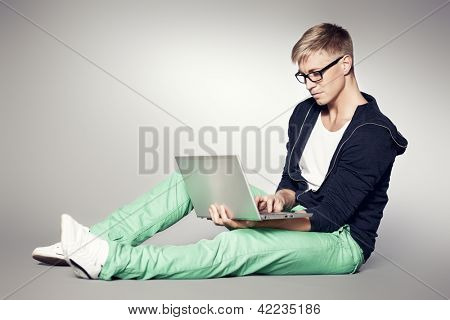 Young handsome man sitting on the floor while working on laptop isolated on grey background.
