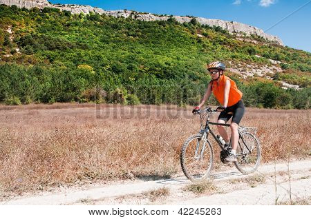 Active bicyclist riding at the countryside against moontain