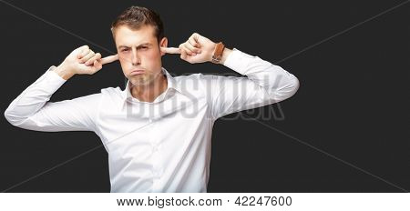 Portrait Of Young Man With Finger In His Ear On Black Background