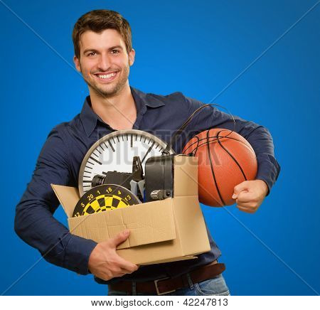 Happy Young Man Holding Cardboxes On Blue Background