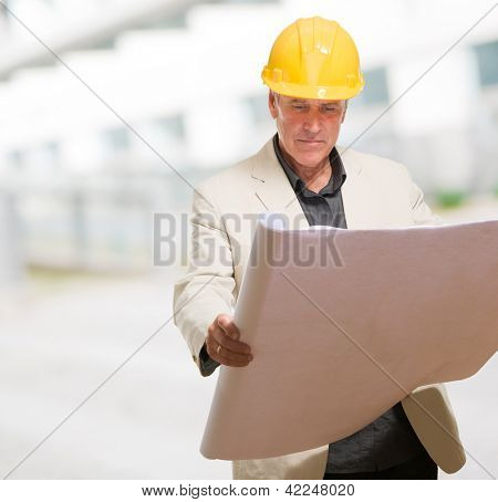 Mature Man With Hard Hat And Paper against an abstract background