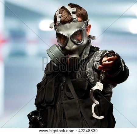 Soldat mit A Gasmaske Holding Handschellen in einer garage
