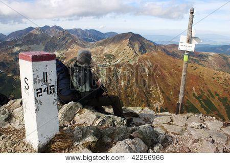 man sitting on the Slovakia Poland border - Rohace mountains - West Tatra Mountains