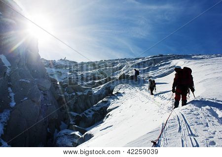 group of climbers on rope on glacier - sunny day on mountain