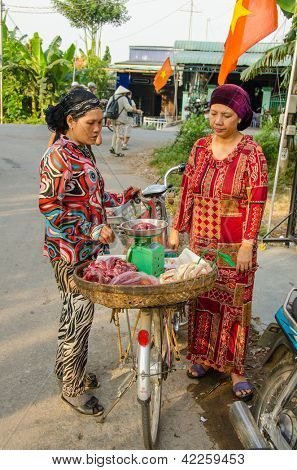 CHAU DOC, VIETNAM - JANUARY 3: Unidentified seller of raw meat sells her products to an identified client from a makeshift stand on her bicycle on the street on January 3 2013 in Chau Doc, Vietnam