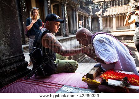 SIEM REAP, CAMBODIA - DEC 13: Hindu Brahmin blesses tourists in one of the temples of Angkor Wat complex, Dec 13, 2012 Siem Reap, Cambodia. It is the country's prime attraction for visitors.