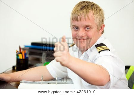 Young Handicapped Pilot Showing Thumbs Up In Office.