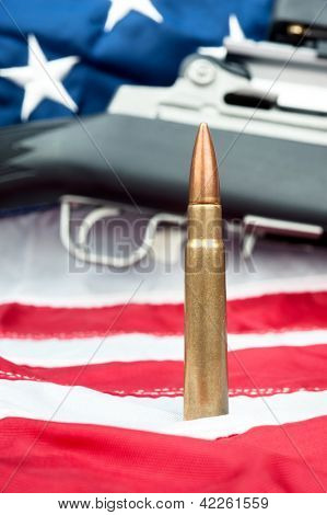 A single bullet in front of an assault rifle sitting on an American flag.