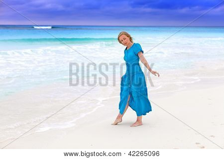 The woman in a long blue dress on the stormy sea coast