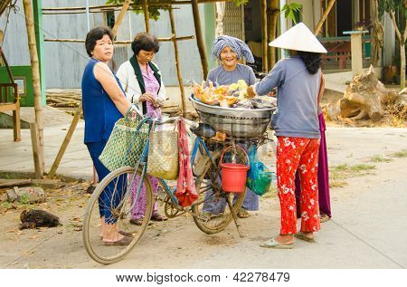 CHAU DOC, VIETNAM - JANUARY 3: Unidentified seller of raw chickens sells her products to local women from a makeshift stand on her bicycle on the street on January 3, 2013 in Chau Doc, Vietnam