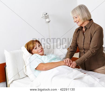 Old sick woman getting a senior visitor in the hospital