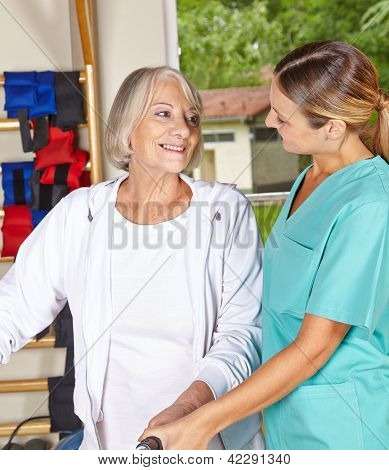 Senior woman at remedial gymnastics looking at physiotherapist