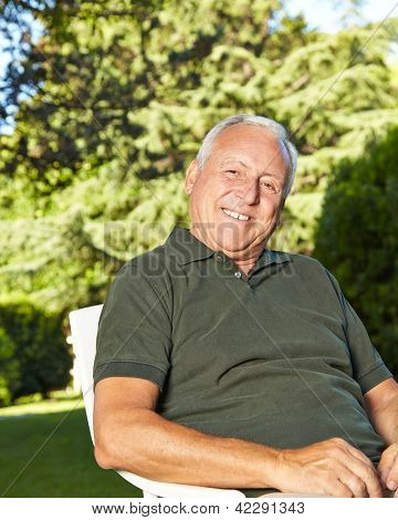 Happy old man sitting in a summer garden