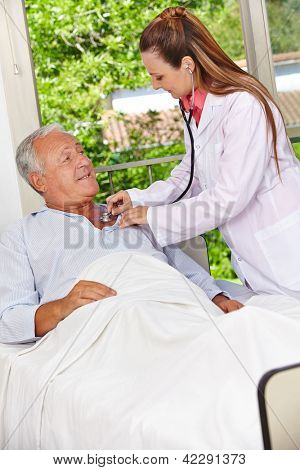 Doctor auscultating patient in hospital bed with stethoscope