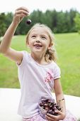 picture of bing  - Happy young girl holding bowl full of bing cherries in park - JPG