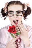 picture of dorky  - Pretty Girl Wearing Dorky Eye Glasses Expressing Shock While Holding A Red Rose Flower In A Valentines Day Concept Isolated Over White Background - JPG