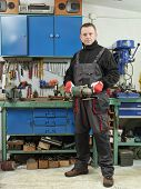 stock photo of locksmith  - Locksmith holding angular grinder while posing in his workshop - JPG