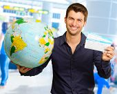 picture of boarding pass  - Young Man Holding Globe And Boarding Pass - JPG