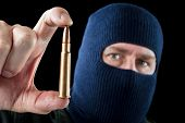 image of extremist  - A terrorist wearing a ski mask as a disguise holds out a large automatic rifle bullet - JPG