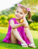 foto of little girls photo-models  - Photo of cute little girl sitting on green grass on backyard and holding in hand colorful lollipop - JPG