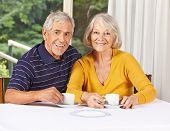 Happy senior couple drinking coffee in a retirement home
