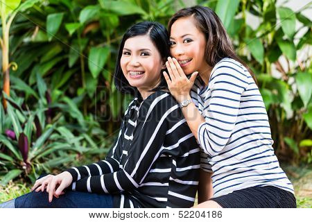 Two Indonesian girlfriends in a tropical environment, they look into the camera and whisper