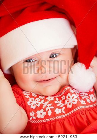 Closeup portrait of beautiful newborn baby wearing red Santa Claus hat, Christmas party, New Year celebration, happiness concept