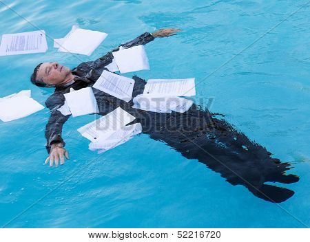 Senior Man Floating Among Papers In Water