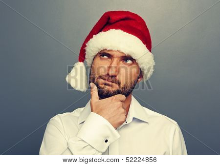thoughtful man in christmas hat looking up over grey background