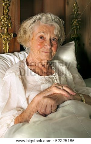Senior Lady In Her Nightgown In Bed