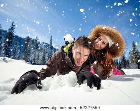 Portrait of joyful woman throwing snowball at man