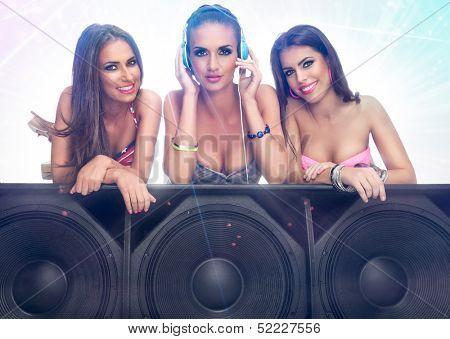 Three cute girls listening music on large speaker