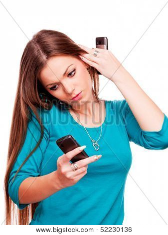 Beautiful young brunette talking on the mobile phone and holding mobile phone in each hand - isolated on white