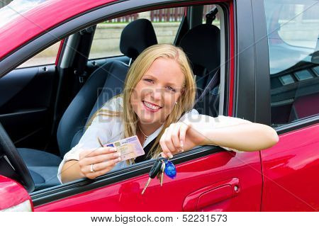a young woman sitting in her car and proudly shows her license after passing the driving test.