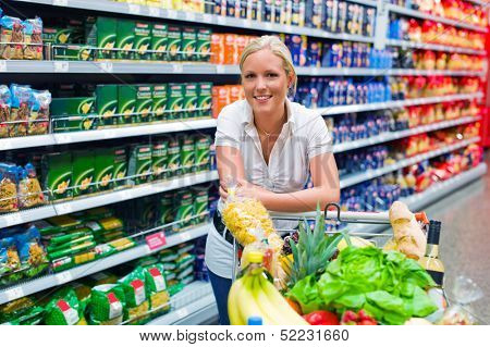 a young woman shopping in the supermarket. full cart.